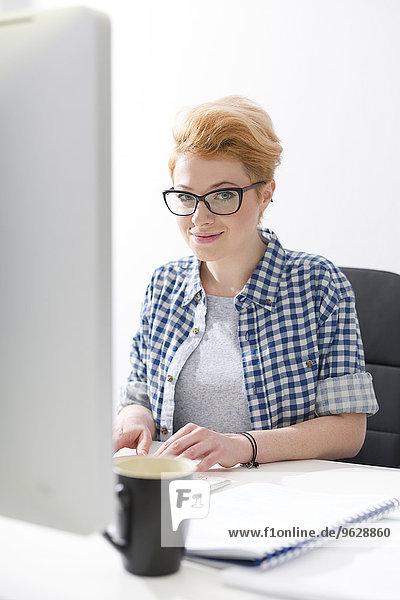 Lächelnde junge Frau bei der Arbeit am Schreibtisch