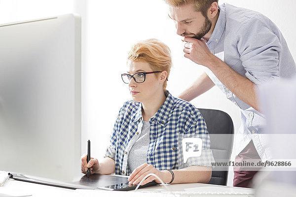 Junge Frau und Mann mit digitalem Tablett am Schreibtisch