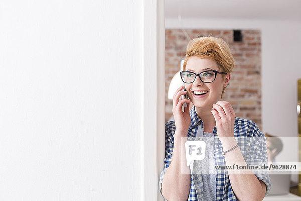 Lächelnde junge Frau am Handy im Büro