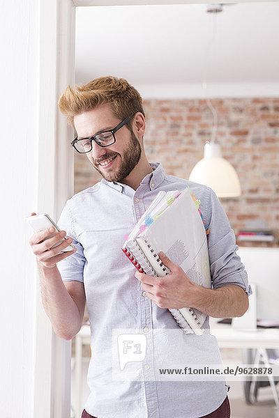 Lächelnder junger Mann mit Handy und Ordner im Büro