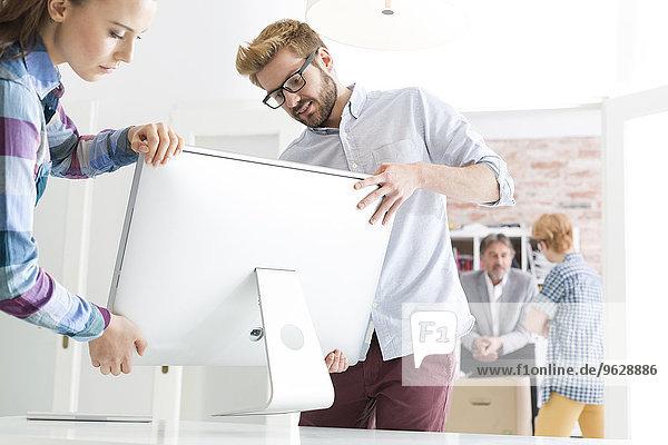 Junger Mann und Frau mit Computerbildschirm im Büro