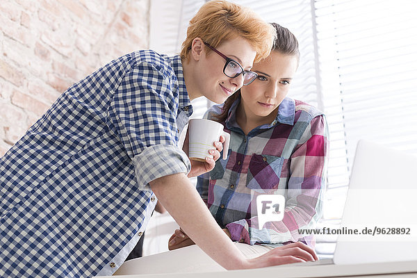 Two young women in office working at laptop
