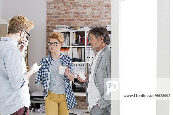 Drei Geschäftsleute sprechen im Büro