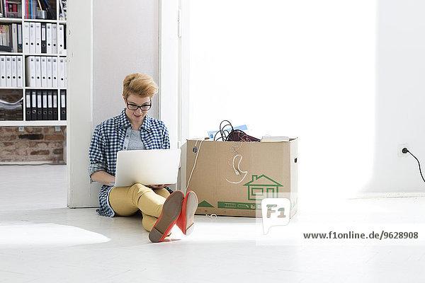 Junge Frau im Büro auf dem Boden sitzend mit Laptop neben dem Karton