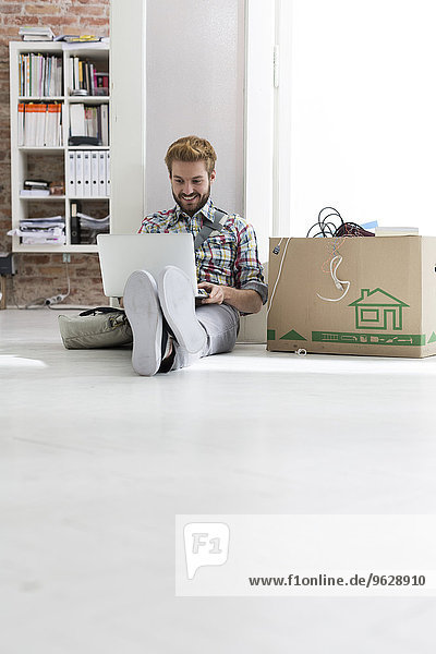 Young man sitting on floor in office using laptop next to cardboard box