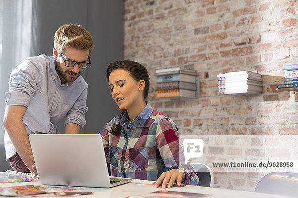 Junge Frau und Mann mit Laptop im Büro