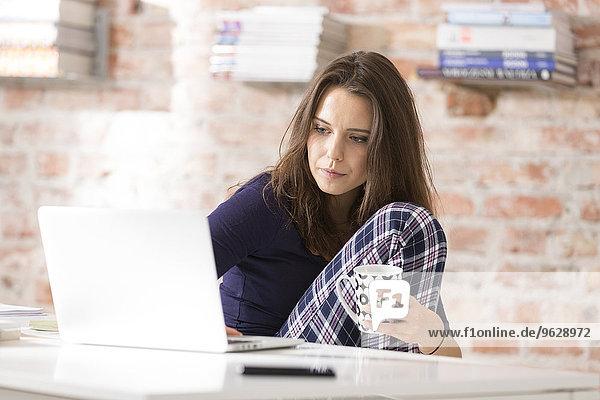 Junge Frau im Schlafanzug mit Laptop