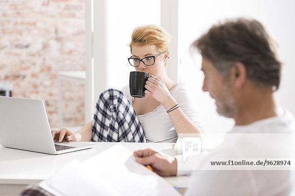 Junge Frau im Schlafanzug mit Laptop und Mann beim Lesen