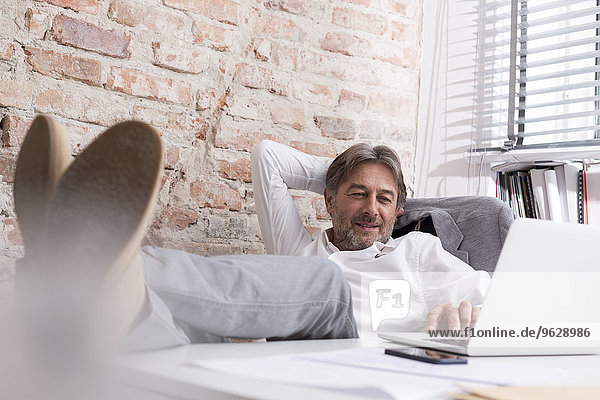 Entspannter Geschäftsmann mit Laptop am Schreibtisch