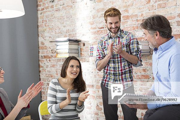 Geschäftsleute beim Händeklatschen einer Präsentation im Sitzungssaal