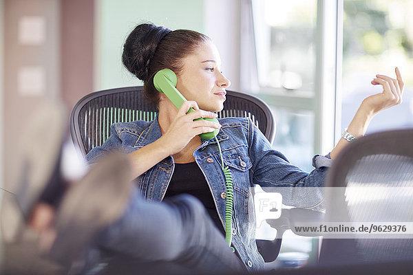 Kreatives  professionelles Telefonieren mit erhobenen Füßen im Büro