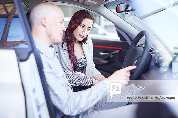 Pärchen beim Autohändler bei der Untersuchung des Fahrzeuginnenraums