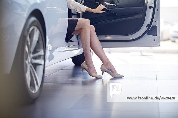Frau beim Autohändler im Auto sitzend