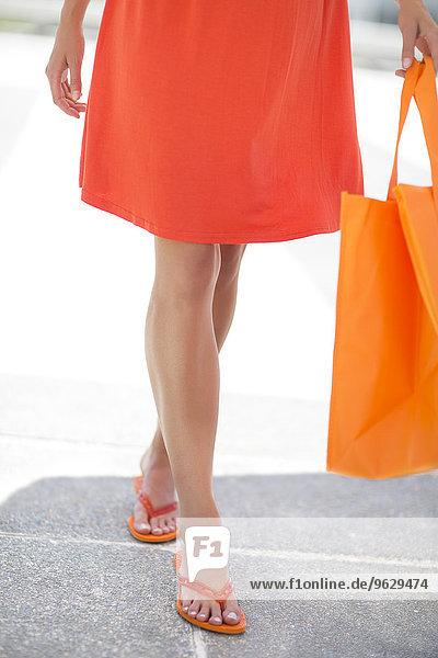 Orange gekleidete Frau mit Einkaufstasche und Flip-Flops