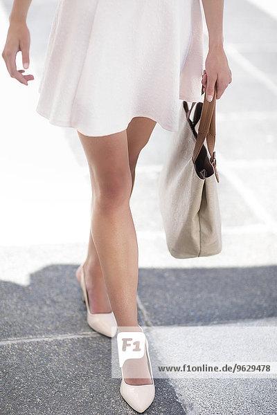 Weiß gekleidete Frau mit Handtasche