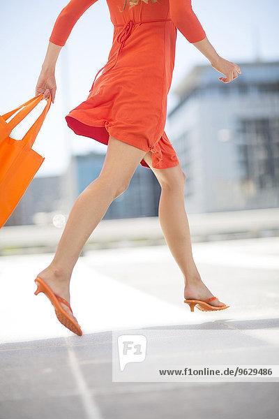 Orange gekleidete Frau mit Einkaufstasche