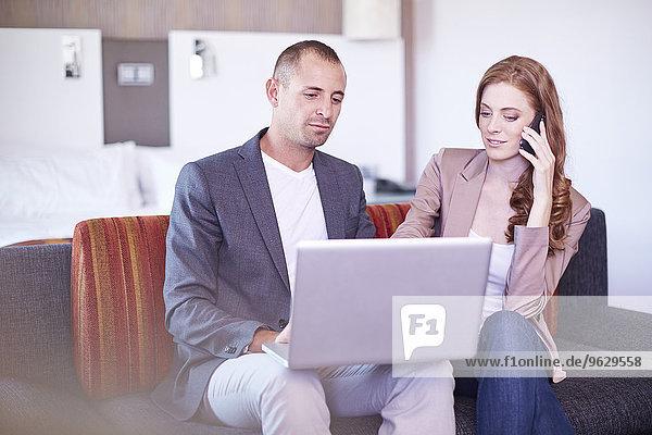 Geschäftsmann und Geschäftsfrau mit Laptop und Handy im Hotelzimmer