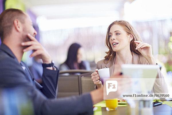 Geschäftsmann und Geschäftsfrau im Gespräch am Esstisch