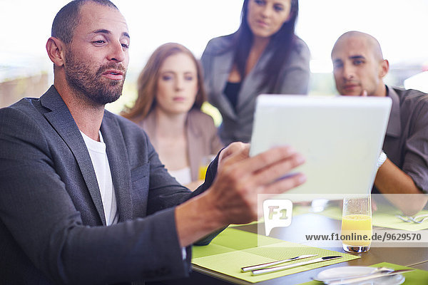 Geschäftsmann zeigt den Kollegen am Esstisch digitales Tablett