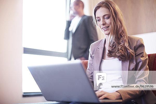 Businesswoman using laptop in hotel room
