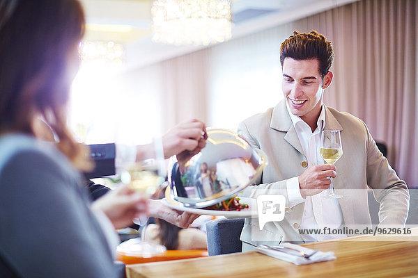 Geschäftsmann sieht Kellner beim Anheben der Servierkuppel im Hotelrestaurant
