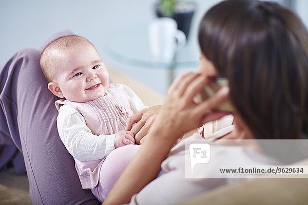 Mutter mit Baby auf der Couch spricht auf dem Handy
