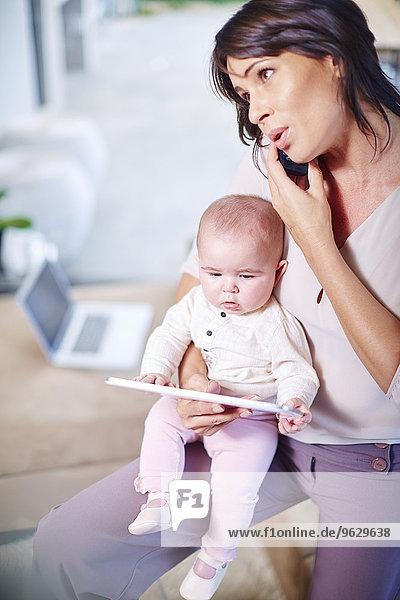 Mutter sitzt mit Baby auf der Couch und spricht am Handy.