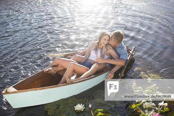 Verspieltes junges Paar in einem Ruderboot auf einem See