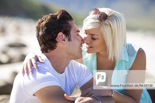 Junges Paar küsst sich am Strand