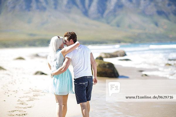 Ein glückliches junges Paar geht am Strand spazieren.