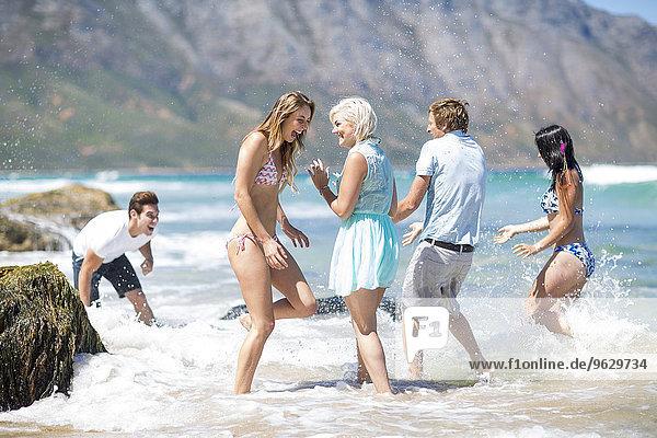 Playful friends splashing in the sea