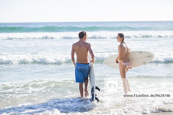 Junges Paar mit ihren Surfbrettern am Meer
