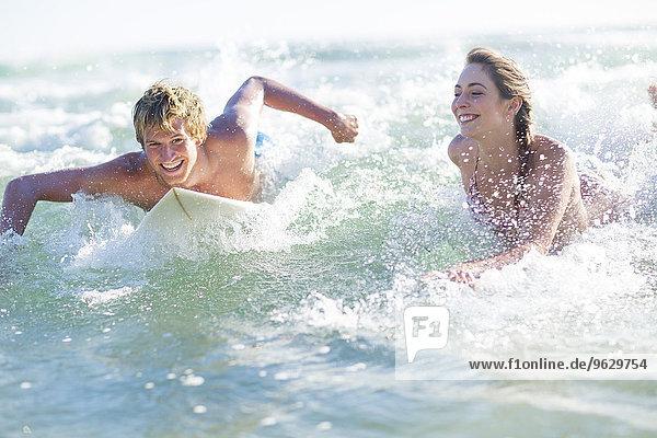 Glückliches junges Paar auf Surfbrettern im Meer liegend
