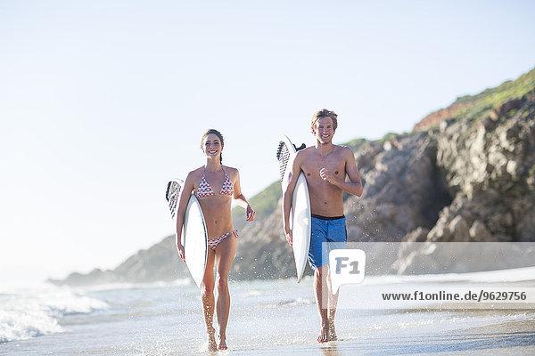 Junges Paar  das mit seinen Surfbrettern am Strand spazieren geht.