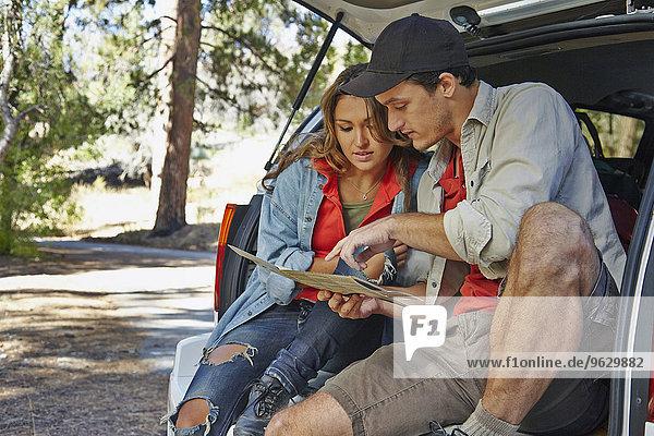 Junges Paar  das auf dem Kofferraum sitzt und auf Karte zeigt  Los Angeles  Kalifornien  USA