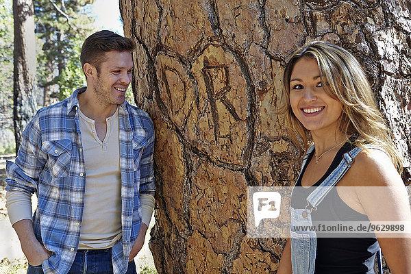 Porträt eines jungen Paares im Wald neben dem Herzschnitt am Baumstamm  Los Angeles  Kalifornien  USA