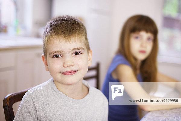 Portrait des Jungen mit Schwester am Küchentisch