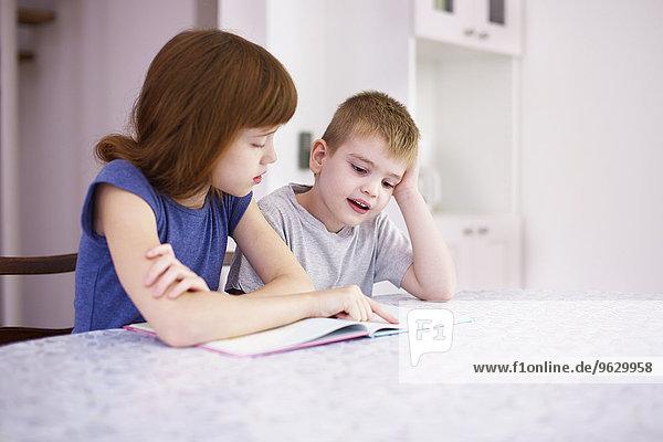 Mädchen-Lesebuch mit Bruder am Küchentisch