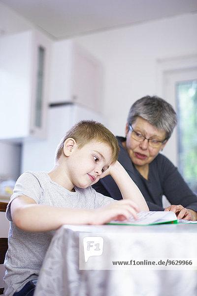 Großmutter Lesebuch mit gelangweiltem Enkel am Küchentisch