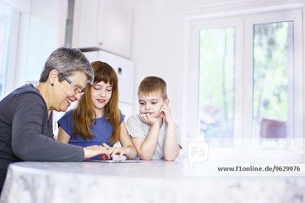 Großmutter und Enkelkinder mit digitalem Tablett am Küchentisch