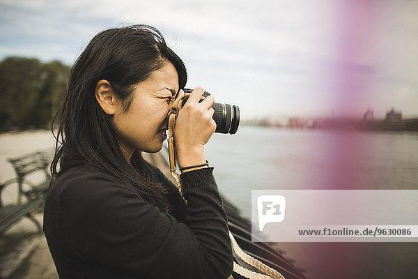 Junge Frau beim Fotografieren im Freien
