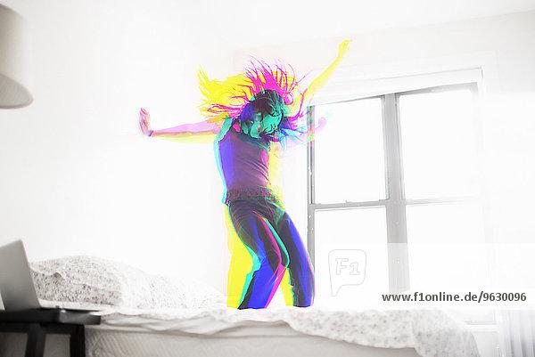 Junge Asiatin tanzt auf dem Bett Junge Asiatin tanzt auf dem Bett