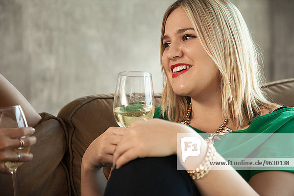 Two female friends sitting on sofa  drinking wine