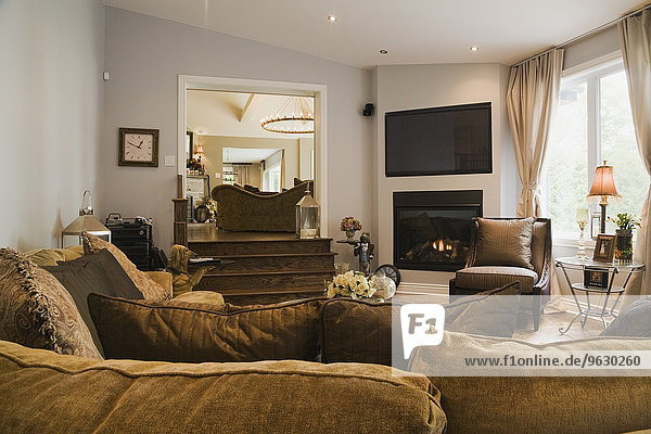 Living room with fireplace and L-shaped sofa in luxury home