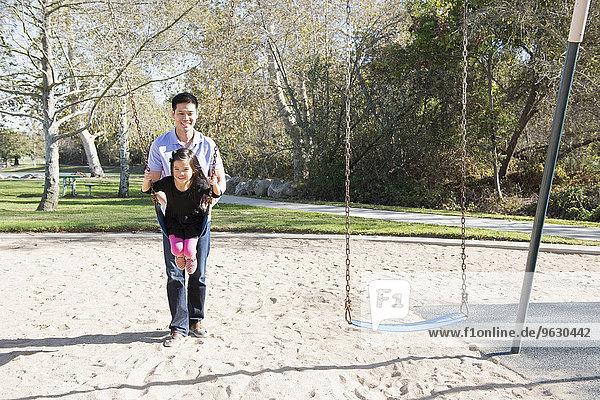 Erwachsener Mann schiebt Tochter auf Spielplatz Schaukeln im Park