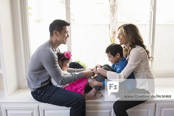 Erwachsenes Paar und zwei Kinder sitzen auf einem Fensterplatz im Wohnzimmer.