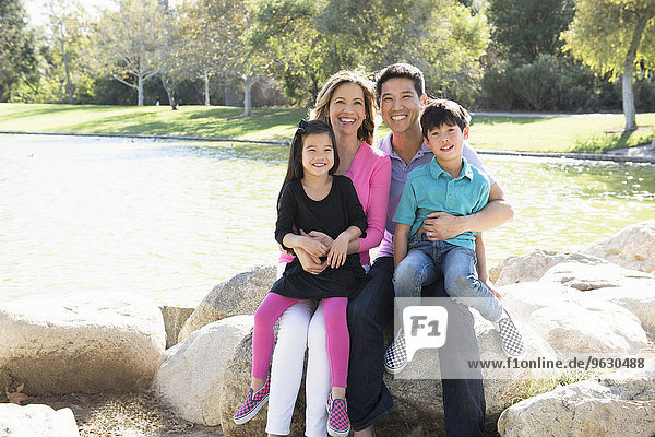 Portrait of mature couple and two children sitting on rocks in park