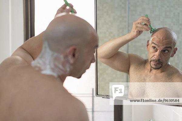 Blick über die Schulter des reifen Mannes beim Rasieren des Kopfes im Bad