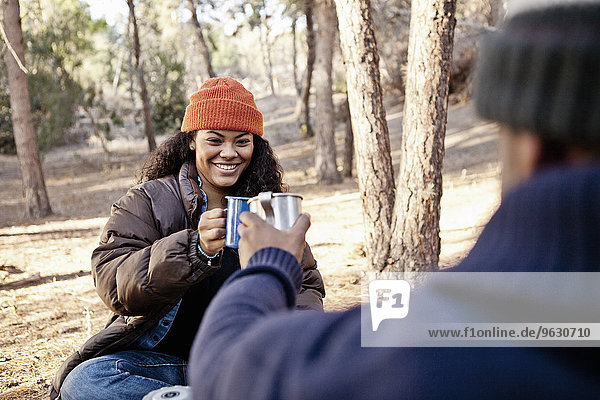 Junges Camping-Paar im Wald sitzend  mit Kaffeebechern anstoßend
