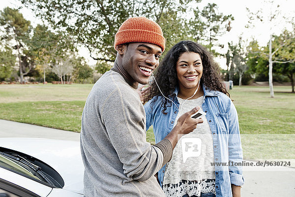 Portrait of young couple in car park sharing smartphone music